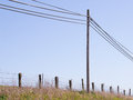 Simple elements in a rural scene telephone pole and wires wire fence and wood fence posts long scruffy grass blue sky Stock Image