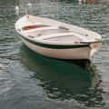 A simple fishing boat very white seems to float over the clear waters of the harbor at portofino italy Stock Images