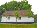 Simple old traditional house with a white facade the beauty of wall of farmhouse small trees in front of the on the there are two Stock Images