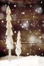 Simple rustic christmas trees in snow two cut out of wood standing front of a wooden wall with falling snowflakes for a festive Royalty Free Stock Images