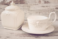 Simple rustic white crockery, empty dishes. A large cup of coffee in front angel and porcelain jar with lid. Wooden background, sh Royalty Free Stock Photo