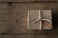 Simple string tied box with vintage style tag on old oak wood ta a gift or package a blank label shot overhead an planked table Royalty Free Stock Photo