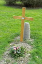 Simple tomb wood cross and flower on a cemetery in green grass Royalty Free Stock Images