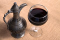 Simple view of pewter flagon and red vine in the glass wine on burlap fabric Royalty Free Stock Image