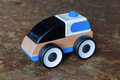 Simple wood and plastic toy police car isolated on a granite floor Royalty Free Stock Photography