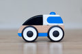 Simple wood and plastic toy police car isolated on a wooden floor Royalty Free Stock Photos