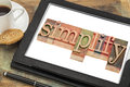 Simplify word typography text in letterpress wood type on a digital tablet with a cup of coffee Stock Photography