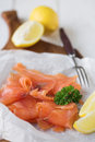 Simply smoked salmon simple shot of organic lemon with parsley garnish displayed on a board shallow dof Royalty Free Stock Image
