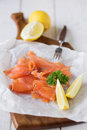 Simply smoked salmon simple shot of organic lemon with parsley garnish displayed on a board shallow dof Royalty Free Stock Photos
