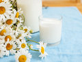 Simply stylish wooden kitchen with bottle of milk and glass on table, summer flowers camomile, healthy food morning Royalty Free Stock Photo