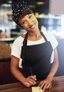Sincere attractive young coffee shop owner female african american standing in an apron and bandanna behind the counter giving the Royalty Free Stock Image