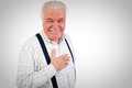 Sincere senior man with his hand on his heart looking at the camera a warm friendly smile upper body studio portrait grey Royalty Free Stock Photo