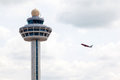 Singapore changi airport traffic controller tower with plane tak international airplane taking off in the background the unique Stock Images