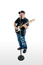 Singer guitarist isolated on white looking right a with black shirt hat and blue jeans at an angle singing and playing Stock Photo