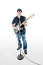 Singer guitarist isolated on white soloing a with black shirt hat and blue jeans at an angle singing and playing Stock Photo