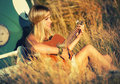 Singing attractive blonde woman on a field and playing guitar Stock Image