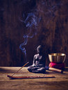 Singing bowl buddha wood joss stick lit and on with Stock Image