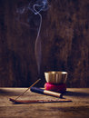 Singing bowl wood joss stick lit on with Stock Photo