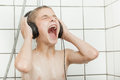Singing child with earphones in shower stall Royalty Free Stock Photo