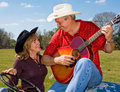 Singing Cowboy & Wife Flirting Royalty Free Stock Photography