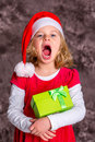 Singing girl with Santa- cap and present Royalty Free Stock Photo
