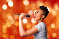 Singing kareoke woman with microphone beautiful teenager concert artist holding on red orange blurred lights background Royalty Free Stock Photography