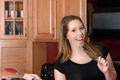 Singing into a wisk an attractive young woman wearing black top is having fun and in the kitchen while holding spatula in the Royalty Free Stock Image