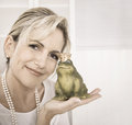 Single attractive older woman with a frog king in her hands. Royalty Free Stock Photo