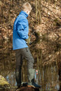 Single boy in blue jacket at pond fishing alone Royalty Free Stock Photo