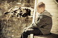 Single boy in jacket sitting on dock long telephoto side view of with hood wooden over water during sunny cool day Royalty Free Stock Photos