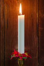 Single burning candle with decorated candle ring at a blurred background of old wooden wall Stock Images