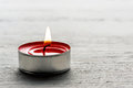 Single burning red tealight candle close up of a in a metal base on a white textured background with copyspace for your message or Stock Photos