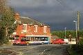 Single deck bus at stop outside village pub. Stock Photos