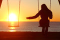 Single or divorced woman alone missing a boyfriend while swinging on the beach at sunset Royalty Free Stock Images