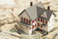 Single family house on pile of money concept real estate Stock Photo