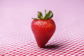 Single fresh strawberry standing up on red gingham tablecloth Royalty Free Stock Images