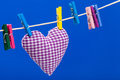 Single heart on clothesline with clothespins Stock Photos