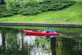 Single kayaker swims on a city channel in Riga