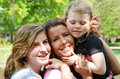 Single mom with daughters up close shot of and her two hanging at the park and hugging each other Stock Image