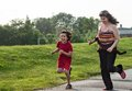 Single mother having fun with her child running and in a park Royalty Free Stock Image