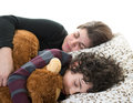 Single mother sleeping with her son and a teddy bear candid picture of a small family normal life at home hispanic family over Royalty Free Stock Photos