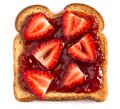 Single Piece of Wheat Bread Toasted with Strawberry Jam Isolated on a White Background Royalty Free Stock Photo