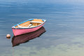 A single pink boat in clear blue water with reflection Stock Photos