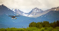 Single prop airplane pontoon plane water landing alaska a bush performs in with chugach mountains in the background Stock Photos