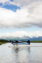 Single prop airplane pontoon plane water landing alaska last frontier a bush performs take off in with chugach mountains in the Stock Images