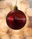 Single Red Christmas Ornament hanging in front of lights Royalty Free Stock Photo