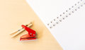 Single red hole punch and clothespin with open white notebook on table surface Stock Image
