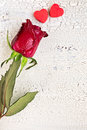Single red rose with two small red cookies in shape of heart on ols white wooden background top view Stock Image