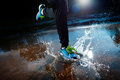 Single runner running in rain and making splash puddle Stock Photos