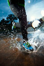 Single runner running in rain and making splash puddle Stock Image